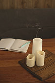 Notebook for diary entries on the table with candles.