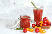 Tomato juice, sauce, pasta and ingredients on a concrete table. The concept of detox diet and weight loss, natural nutrition, healthy and natural foods. Summer drinks,