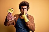 Young handsome butcher man holding meet steak standing over isolated yellow background asking to be quiet with finger on lips. Silence and secret concept.