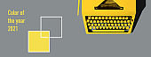 Yellow bright typewriter on gray background. Color of the year 2021