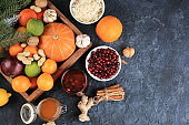 Healthy natural food for the flu and colds. Selection of fresh fruits and vegetables with vitamin C, tangerines, cabbage, cranberries, cinnamon, honey on a concrete table. Organic virus protection products,