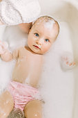 Happy laughing baby taking a bath playing with foam bubbles. Little child in a bathtub. Infant washing and bathing. Hygiene and care for young children. face of a little baby in the bathroom