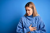 Young beautiful blonde woman wearing winter wool sweater over blue isolated background with hand on stomach because indigestion, painful illness feeling unwell. Ache concept.