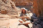 Young beauitufl hiker woman trekking natural orange mountain doing yoga pose on summer holidays