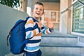 Adorable caucasian student boy smiling happy saying goodbye at the school.