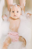 Happy laughing baby taking a bath playing with foam bubbles. Little child in a bathtub. Infant washing and bathing. Baby looking upwards in a plastic tub full of foam.