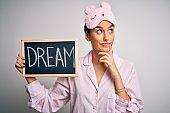 Young beautiful woman wearing pajama and sleep mask holding blackboard with dream word serious face thinking about question, very confused idea