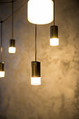 hanging retro incandescent lamp on a background of wooden blinds.Creative loft style lamp with shining lightbulb.Hanging thread lamps.lighting suspended at different levels from the ceiling