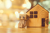 Wood robot sitting in solitude on the floor and looking sad or depressed with wood house .