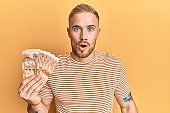 Young caucasian man holding south african 20 rand banknotes scared and amazed with open mouth for surprise, disbelief face