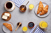 French breakfast background. Top view of gray table, croissants, orange juice, coffee, jam and butter