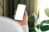 Woman holding and touching blank screen template smart phone. Smart phone screen is empty.