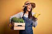 Young beautiful brunette gardener woman wearing apron and hat holding box with plants pointing and showing with thumb up to the side with happy face smiling