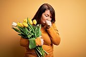 Beautiful plus size woman holding romantic bouquet of natural tulips flowers over yellow background feeling unwell and coughing as symptom for cold or bronchitis. Health care concept.