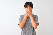 Young chinese man wearing casual t-shirt standing over isolated white background shocked covering mouth with hands for mistake. Secret concept.