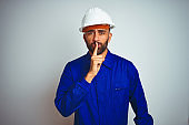Handsome indian worker man wearing uniform and helmet over isolated white background asking to be quiet with finger on lips. Silence and secret concept.