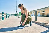 Young blonde sportswoman wearing sportswear tying her shoelaces at the city