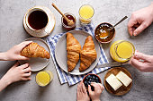 Dad with kids eating breakfast in the morning. Top view of a gray table, croissants, orange juice, coffee, jam and butter. Stay home concept