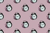 Many black classic style alarm clock isolated on pink background