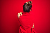 Young beautiful business woman standing over red isolated background Hugging oneself happy and positive from backwards. Self love and self care