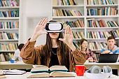 Young Caucasian brunette girl student working with VR simulator in library. Young woman in casual wear and virtual reality glasses sitting at desk and touching air. VR goggles for studying concept