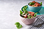 Summer salad of fresh with basil vegetables served in a bowl. A tomato. cucumbers, onions, radishes. sesame seeds and pumpkin seeds Copy space