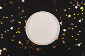 Black background with shiny stars and empty plate mock up
