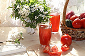 Tomato juice, drink and ingredients on a sunny table. The concept of detox diet and weight loss, healthy and natural food. Summer drinks, vitamins C