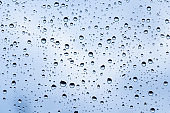 image of raindrops on glass with beautiful blue color.