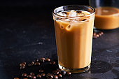 Tasty ice coffee with milk , cold drink in glass on dark background