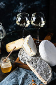 Various types of cheese composition. Gorgonzola, camembert, brie cheese. Roquefort, dor blue. Walnut and wine. Appetizer and gourmet food. Honey in jar