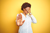 African american business woman over isolated yellow background covering eyes with hands and doing stop gesture with sad and fear expression. Embarrassed and negative concept.