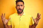 Young indian man wearing polo standing over isolated yellow background crazy and mad shouting and yelling with aggressive expression and arms raised. Frustration concept.