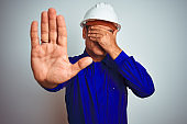 Handsome middle age worker man wearing uniform and helmet over isolated white background covering eyes with hands and doing stop gesture with sad and fear expression. Embarrassed and negative concept.