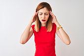 Redhead businesswoman wearing elegant red dress standing over isolated white background with hand on headache because stress. Suffering migraine.