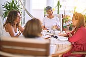 Meeting of middle age women having lunch and drinking coffee. Mature friends smiling happy  at home on a sunny day