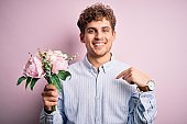 Young blond man with curly hair holding beautiful bouquet over isolated pink background with surprise face pointing finger to himself
