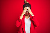 Young beautiful business woman standing over red isolated background suffering from headache desperate and stressed because pain and migraine. Hands on head.