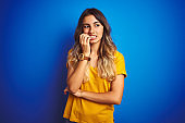 Young beautiful woman wearing yellow t-shirt over blue isolated background looking stressed and nervous with hands on mouth biting nails. Anxiety problem.