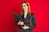 Young beautiful redhead businesswoman wearing suit holding suitcase