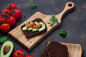 Healthy sandwich with avocado, tomatoes and spices on whole grain bread. Wooden cutting boards on a dark background