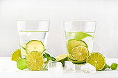 Drink glasses with water ,lime,mint and ice on white background