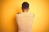 Young indian man wearing t-shirt standing over isolated yellow background Hugging oneself happy and positive from backwards. Self love and self care