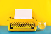 Yellow bright typewriter on a yellow background. Creativity concept