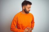 Young indian man wearing orange sweater over isolated white background with hand on stomach because nausea, painful disease feeling unwell. Ache concept.