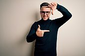 Young handsome caucasian man wearing glasses and casual sweater over isolated background smiling making frame with hands and fingers with happy face. Creativity and photography concept.