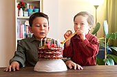 Cute children making birthday party with cake and party confetti. Birthday party and big celebration at home
