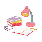 Stack of books, desk lamp, glasses, and a pencil on the table. The student's workplace in the classroom or at home