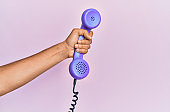 Hispanic hand holding vintage telephone over isolated pink background.