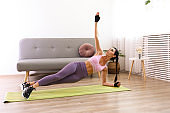 Young fit woman working out at living room of her apartment.